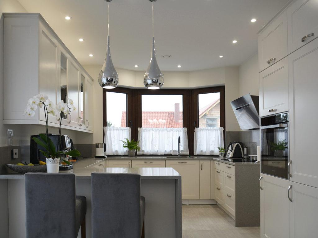 Biała kuchnia z szarymi hokerami w kolorze szarym