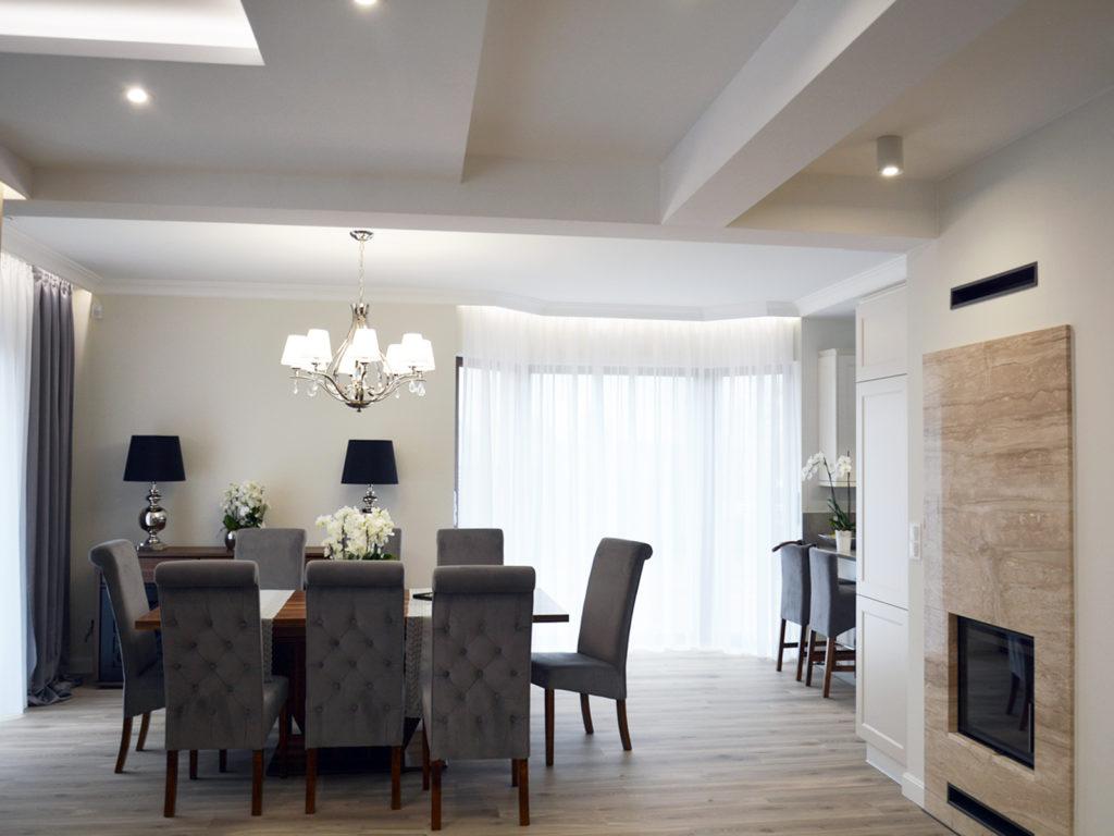 Nowoczesna jadalnia z dużym stołem drewnianym i tapicerowanymi, pikowanym krzesłami