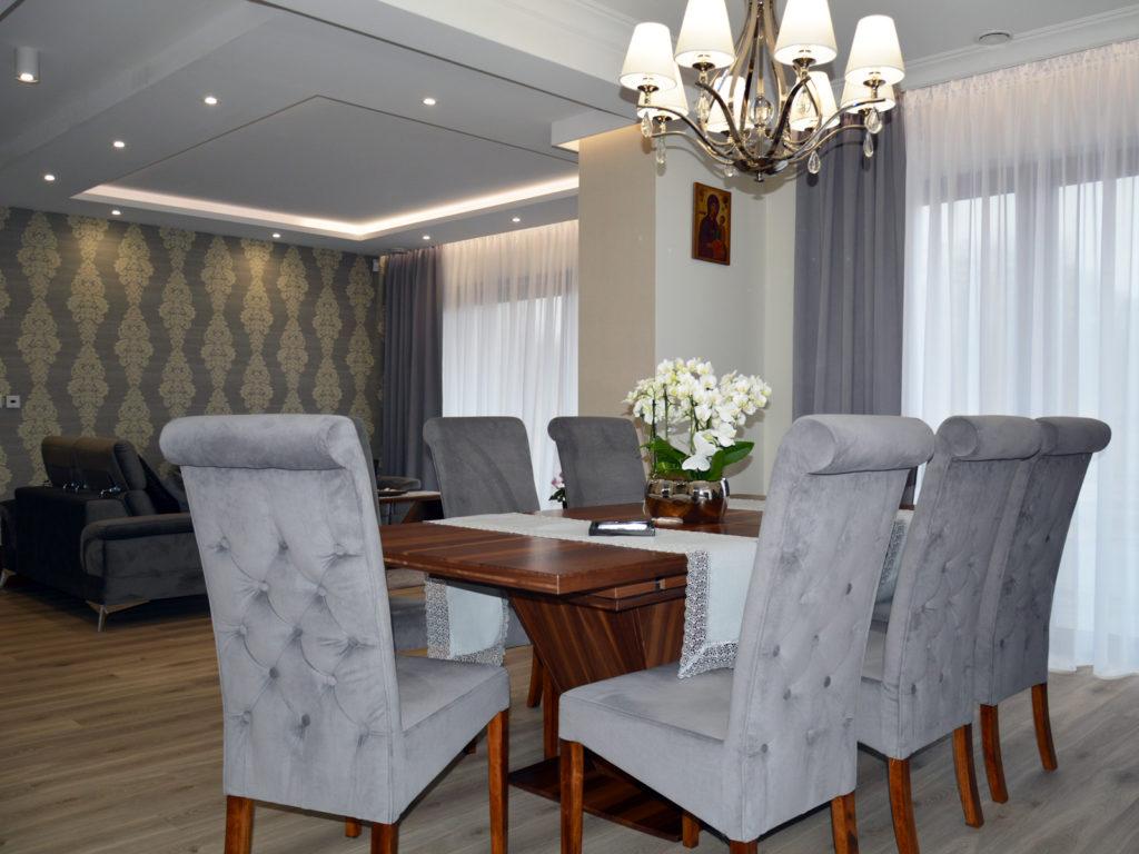 Nowoczesna jadalnia z tapicerowanymi, pikowanym krzesłami oraz lampą wiszącą w stylu hampton