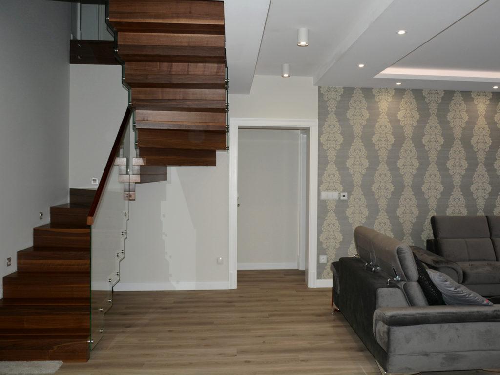 Schody dywanowe ze szkalną balustradą i drewnianym pochwytem