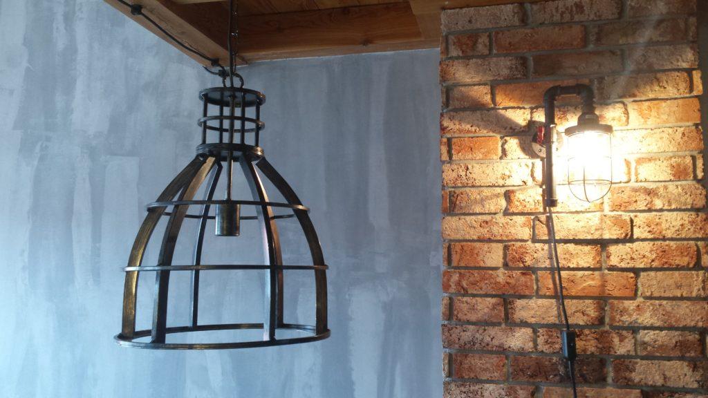 Loftowa lampa z metalu, ściana z fakturą betonu i okładziną z cegły