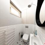 Aranżacja toalety w skandynawski stylu z szafką i armzaturą Roca i lustrem na psku skórzanym
